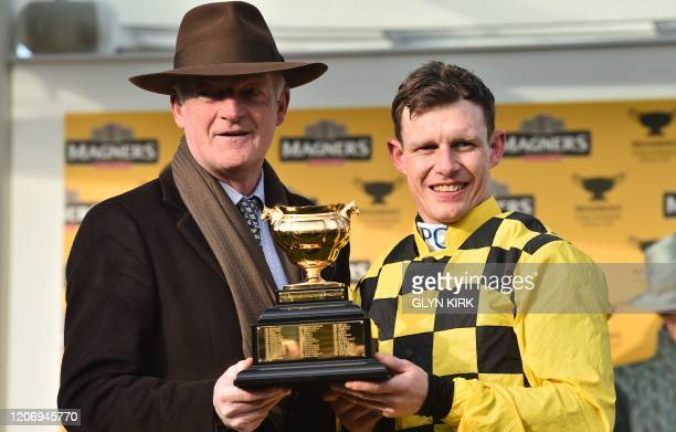 Al Boum Photo's jockey Paul Townend and Irish trainer Willie Mullins pose with the trophy after winning the Gold Cup race on the final day of the...