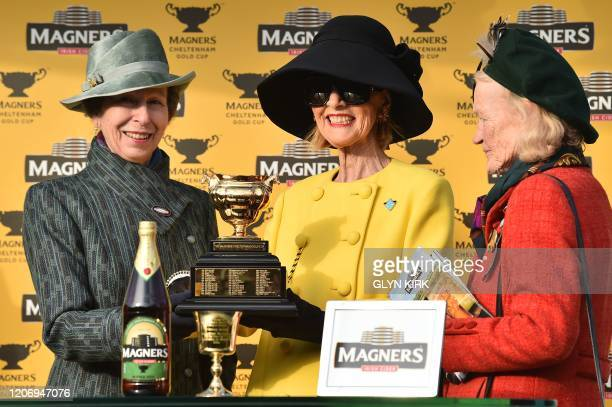 Al Boum Photo's owners pose with the trophy after winning the Gold Cup race on the final day of the Cheltenham Festival horse racing meeting at...