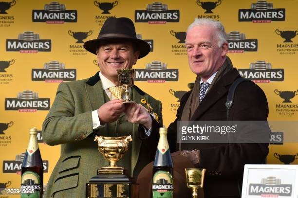Al Boum Photo's trainer Irish trainer Willie Mullins poses with a trophy after winning the Gold Cup race on the final day of the Cheltenham Festival...
