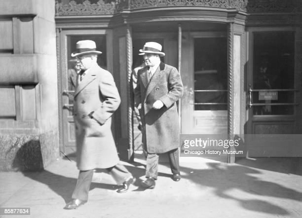 Al Capone, preceded by an unidentified man, exits a revolving door at an unidentified location in Chicago, ca.1920s.