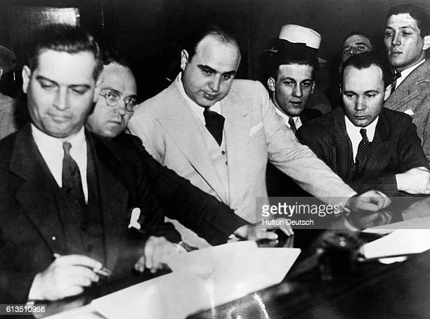 Al Capone the gangster and socalled ruler of the Chicago underworld signs a Bail Bond signalling the beginning of his prosecution for failure to pay...