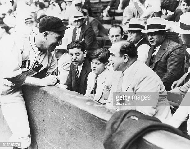 Al Capone with his party at the charity game between the White Sox and Cubs in Chicago in 1931. Gabby Hartnett of the Cubs is shown autographing a...