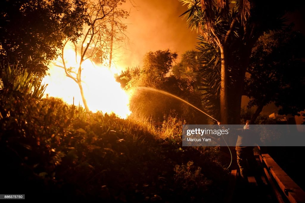 Al Galileo helps water down a backyard of a stranger's home as brush fire encroaches on the property on December 5, 2017 in Ventura, California.
