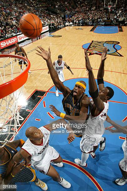 Al Harrington of the Indiana Pacers drives for a shot attempt against Sam Dalembert and Derrick COleman of the Philadelphia 76ers November 9 2003 at...