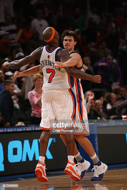 Al Harrington of the New York Knicks chest bumps with teammate Danilo Gallinari during the game against the Philadelphia 76ers at Madison Square...