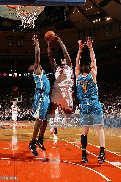 Al Harrington of the New York Knicks goes to the basket under pressure against Emeka Okafor and Darius Songaila of the New Orleans Hornets during the...