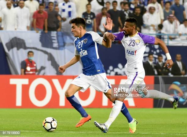 Al Hilal's Achraf Bencharki runs with the ball in front of Al Ain's Mohammed Gharib during the AFC Champions League group stage football match...