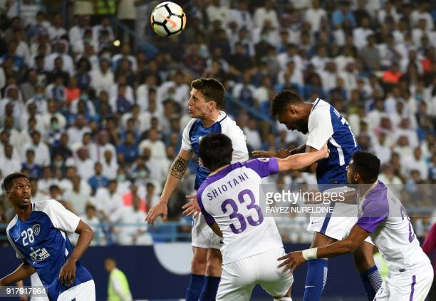 Al Hilal's players head the ball attempting to score against Al Ain during the AFC Champions League group stage football match between Saudi Arabia's...