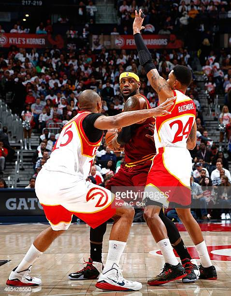 Al Horford and Kent Bazemore of the Atlanta Hawks defend against LeBron James of the Cleveland Cavaliers at Philips Arena on March 6 2015 in Atlanta...