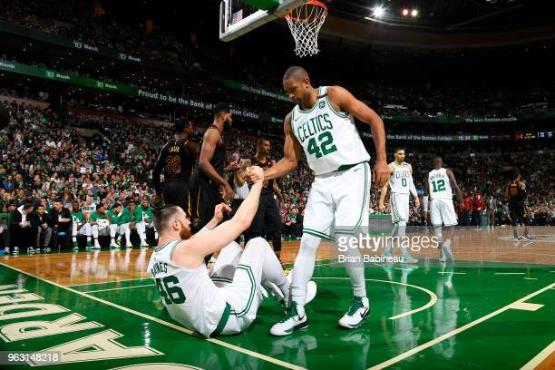 Al Horford helps Aron Baynes of the Boston Celtics from the floor during Game Seven of the Eastern Conference Finals of the 2018 NBA Playoffs between...