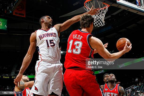 Al Horford of the Atlanta Hawks defends against Mehmet Okur of the New Jersey Nets at Philips Arena on December 30 2011 in Atlanta Georgia
