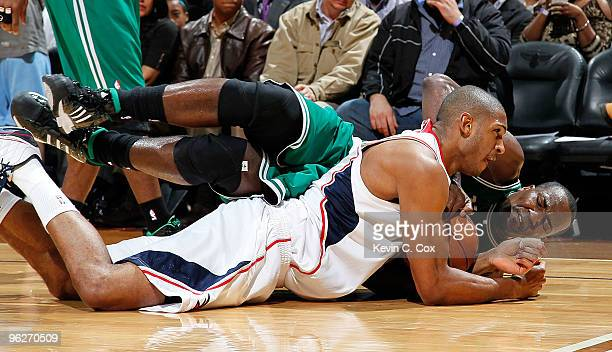 Al Horford of the Atlanta Hawks dives for a loose ball against Kendrick Perkins of the Boston Celtics at Philips Arena on January 29 2010 in Atlanta...