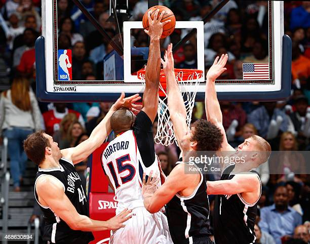 Al Horford of the Atlanta Hawks dunks against Bojan Bogdanovic Brook Lopez and Mason Plumlee of the Brooklyn Nets at Philips Arena on April 4 2015 in...