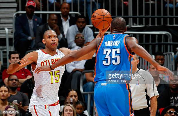 Al Horford of the Atlanta Hawks grabs a rebound against Kevin Durant of the Oklahoma City Thunder at Philips Arena on November 30 2015 in Atlanta...