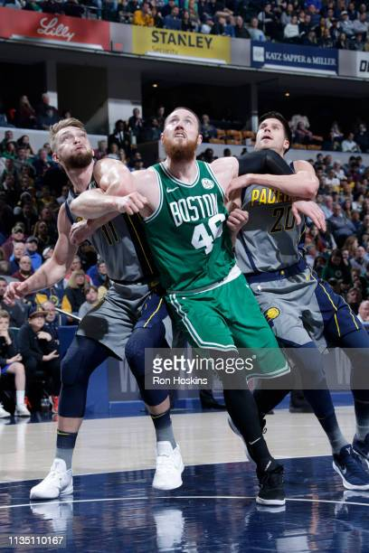 Al Horford of the Boston Celtics defends Domantas Sabonis and Doug McDermott of the Indiana Pacers on April 5 2019 at Bankers Life Fieldhouse in...