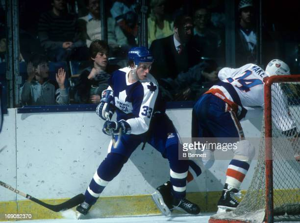 Al Iafrate of the Toronto Maple Leafs battles behind the net with Mikko Makela of the New York Islanders on January 28 1986 at the Nassau Coliseum in...