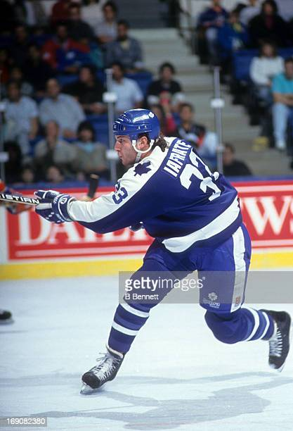 Al Iafrate of the Toronto Maple Leafs shoots during an NHL game against the New York Islanders on November 6 1990 at the Nassau Coliseum in Uniondale...