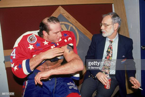 1993 Al Iafrate of the Washington Capitals shows off his bicep tattoo to analyst Stan Fischler who seems marginally interested and holds a cigarette...