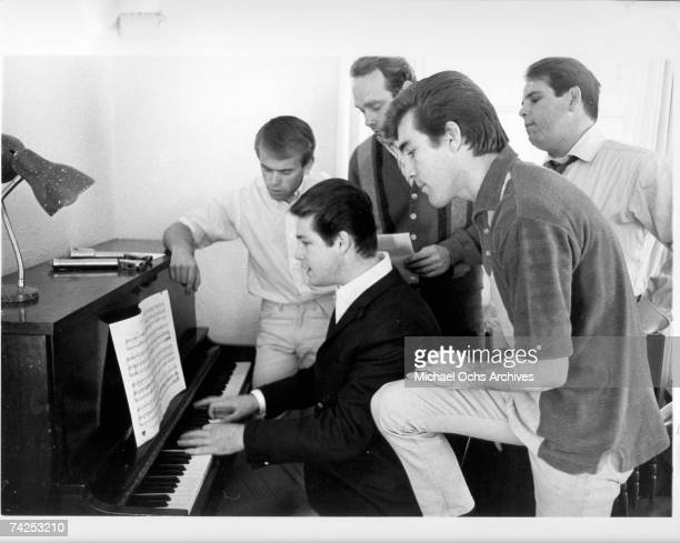 Al Jardine Brian Wilson Mike Love Dennis Wilson and Carl Wilson of the rock and roll band The Beach Boys sing around a piano