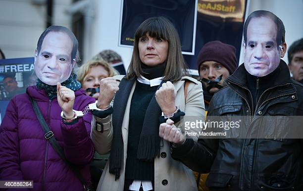 Al Jazeera journalist Sue Turton stands handcuffed to fellow supporters wearing masks depicting President elSisi as they demonstrate in support of...
