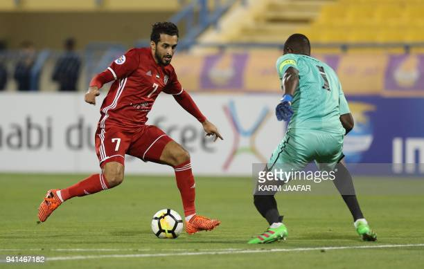 Al Jazira's Ali Ahmed Mabkhout vies with Al Gharafa's goalkeeper Qasem Aboullhamed Burhan during the AFC Champions League match between Qatar's...