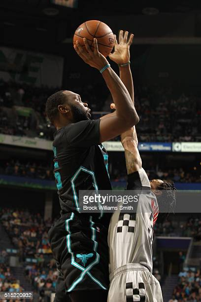 Al Jefferson of the Charlotte Hornets shoots against KJ McDaniels of the Houston Rockets during the game at the Time Warner Cable Arena on March 12...