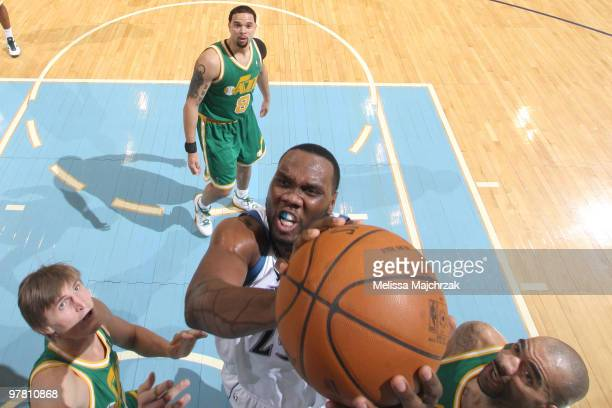 Al Jefferson of the Minnesota Timberwolves goes up for the dunk against Carlos Boozer and Andrei Kirilenko of the Utah Jazz at EnergySolutions Arena...