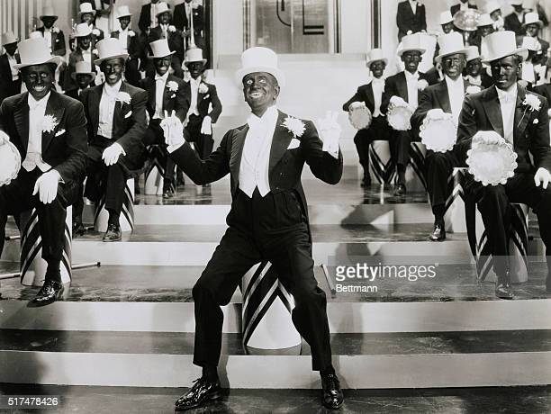 Al Jolson American entertainer famed as black face minstrel singing with white top hat and minstrel tambourine band in a scene from the 1935 film Go...