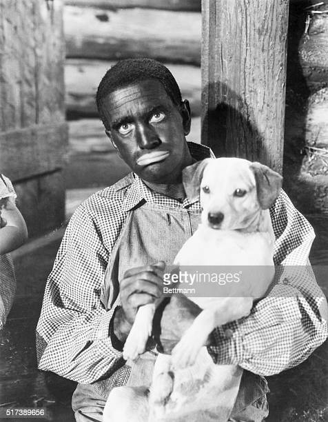 """Al Jolson, in burnt cork for the first time in four years for his role in """"Wonder Bar, is shown holding a dog. Movie released in 1934."""