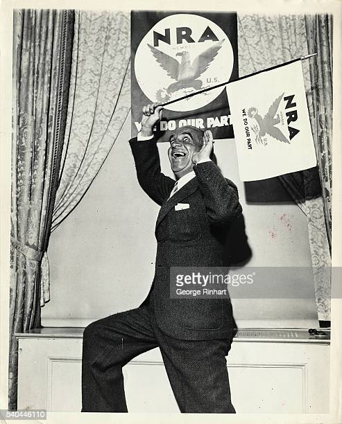 Al Jolson is shown holding an NRA banner and smiling