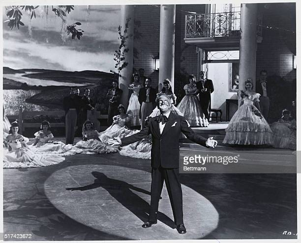 Al Jolson singing Swanee in the 1945 film Rhapsody In Blue He is in black face with he spotlight on him background shows Southern Belles standing in...