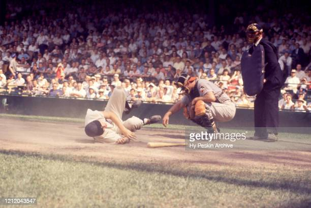 Al Kaline of the Detroit Tigers is knocked down by the pitch as catcher Gus Triandos of the Balitmore Orioles and umpire Eddie Hurley look on during...