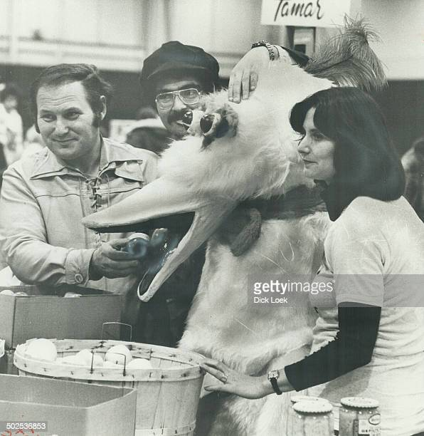 Al King of Kensington Waxman offers an apple to Sesame Street's Big Bird at bazaar's fruit stand