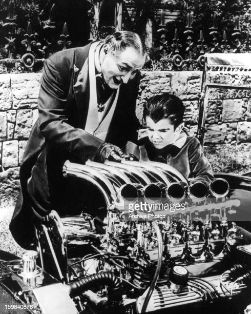 Al Lewis and Butch Patrick working on an engine together in a scene from the television series 'The Munsters' circa 1964
