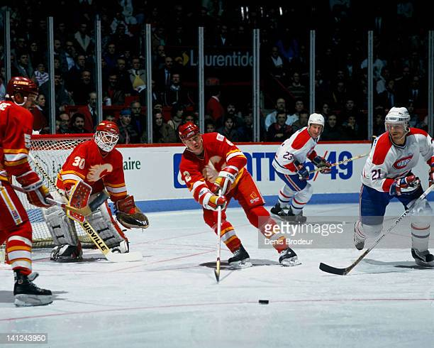 Al MacInnis of the Calgary Flames clears the puck away from his net during a game against the Montreal Canadiens Circa 1990 at the Montreal Forum in...