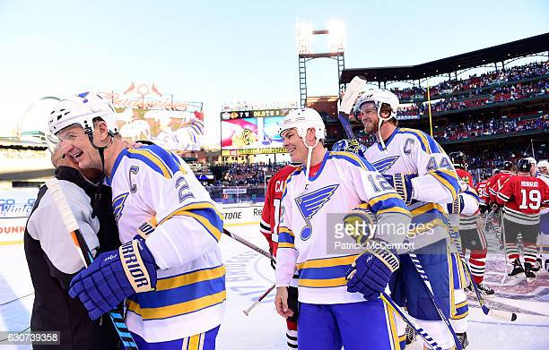 Al MacInnis of the St Louis Blues gets a hug from sportscaster and Chicago Blackhawks alumni Darren Pang as Adam Oates and Chris Pronger of the St...