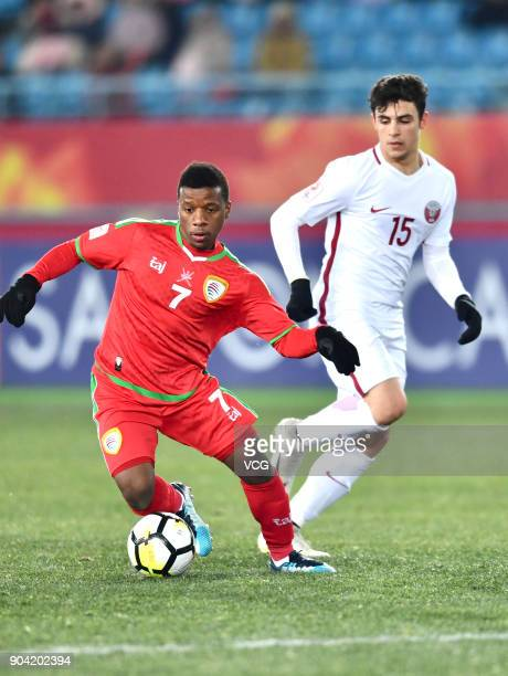 Al Mandhar Al Alawi of Oman and Bassam Al Rawi of Qatar compete for the ball during the AFC U23 Championship Group A match between Oman and Qatar at...