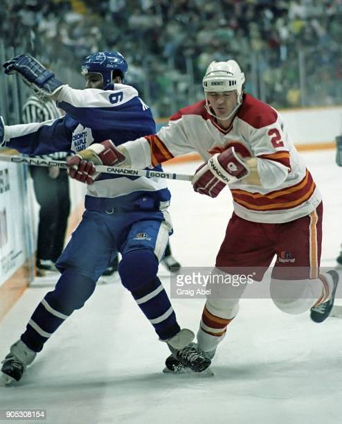 Al Mcinnis of the Calgary Flames skates against Chris Kotsopoulos of the Toronto Maple Leafs during NHL game action on February 20 1986 at the...