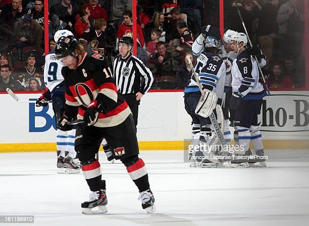 Al Montoya Alex Burmistrov and Blake Wheeler of the Winnipeg Jets celebrate their win as Daniel Alfredsson of the Ottawa Senators skates away during...