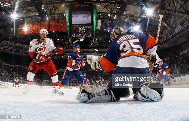 Al Montoya of the New York Islanders makes a glove save off of Eric Staal of the Carolina Hurricanes on April 2, 2011 at Nassau Coliseum in...