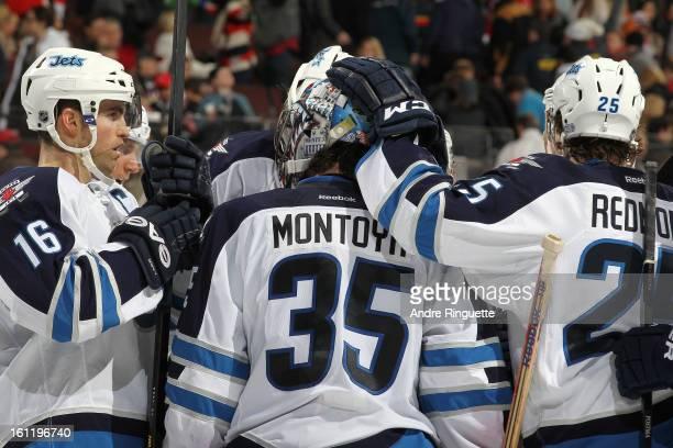 Al Montoya of the Winnipeg Jets celebrates his shutout win against the Ottawa Senators with teammates Andrew Ladd and Zach Redmond on February 9 2013...