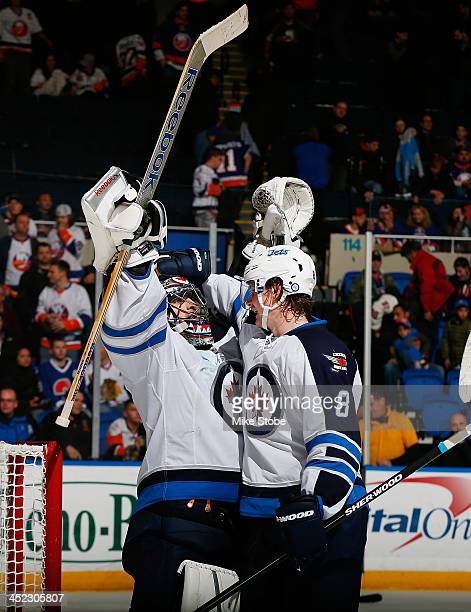 Al Montoya of the Winnipeg Jets celebrates their win with teammate Jacob Trouba after the game against the New York Islanders at Nassau Veterans...