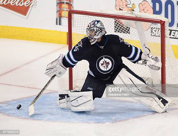 Al Montoya of the Winnipeg Jets knocks the puck away in thirdperiod action in an NHL game against the Ottawa Senators at the MTS Centre on March 8...