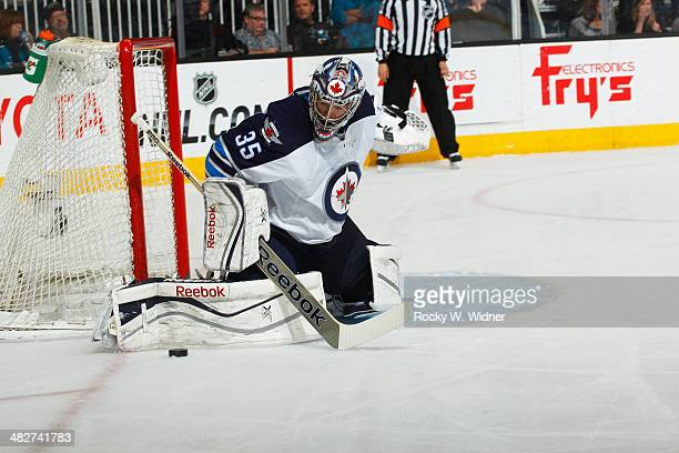 Al Montoya of the Winnipeg Jets saves the puck against the San Jose Sharks at SAP Center on March 27 2014 in San Jose California