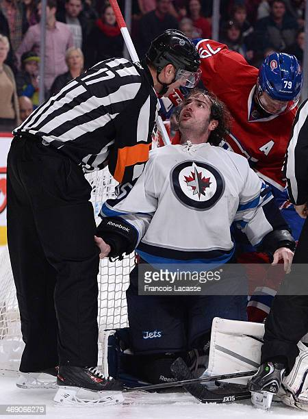 Al Montoya of the Winnipeg Jets speks with referee during the NHL game against the Montreal Canadiens on February 2 2014 at the Bell Centre in...