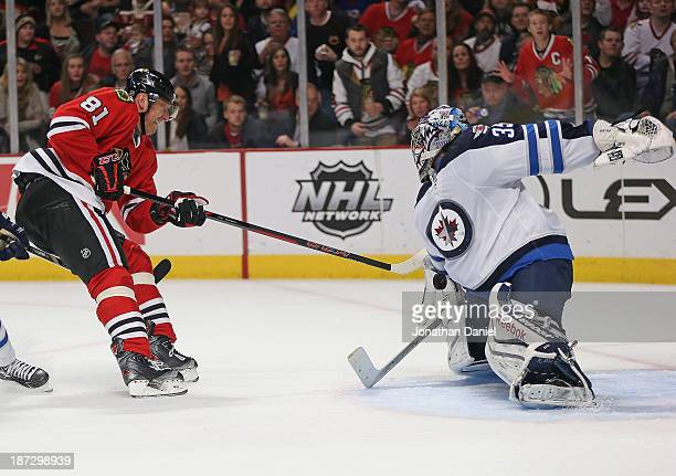 Al Montoya of the Winnipeg Jets stops a shot by Marian Hossa of the Chicago Blackhawks at the United Center on November 6 2013 in Chicago Illinois...