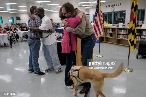 Al Moore center hugs Lisa Hill while her husband Charles rear hugs inmate Herbert WilsonBey at Western Correctional Institution in Cumberland MD on...