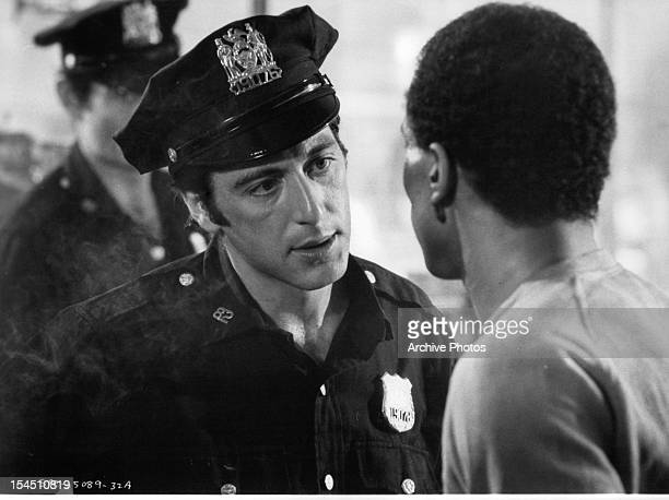 Al Pacino dressed as a police officer speaks to a man in a scene from the film 'Serpico' 1973