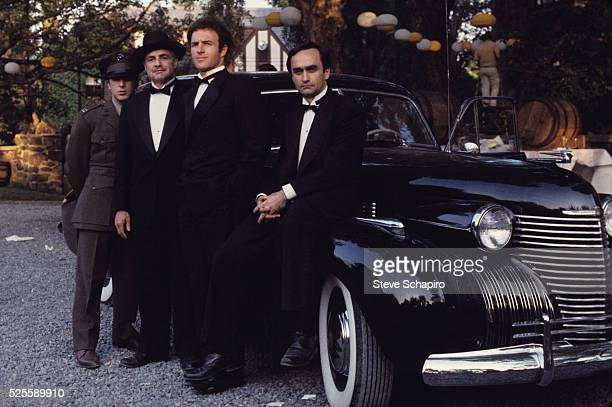 Al Pacino Marlon Brando James Caan and John Cazale stand beside a 1940 Cadillac Fleetwood in the 1972 movie The Godfather