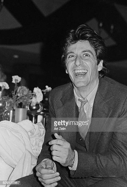 Al Pacino seated at a dinner table laughing circa 1970 New York